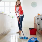 Middle Aged Woman Mopping Kitchen Floor