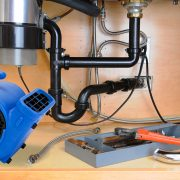 Detail of the plumbing system under a modern kitchen sink, with a plumbers tool tray and equipment. Horizontal format.